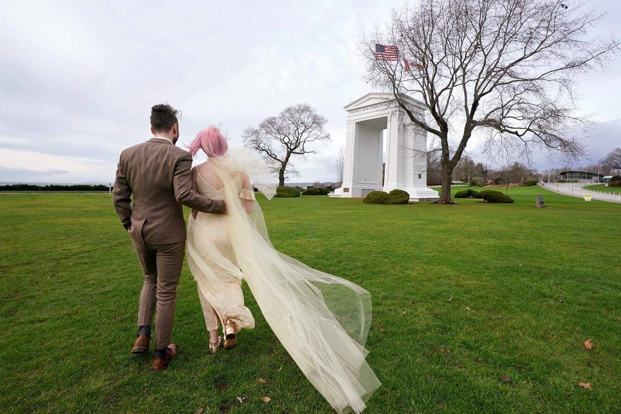 Newlyweds Drew MacPherson, a U.S. citizen from Bellingham, Wash., left, and Faith Dancey, a Canadian from White Rock, B.C., stroll through an otherwise deserted portion of the Peace Arch Historical State Park in the U.S. where it abuts Canada, Sunday, Dec. 20, 2020, in Blaine, Wash. The couple married earlier there after Dancey walked across the border nearby where Canadians have routinely been crossing the ditch to meet with sweethearts, friends and family in the U.S. She planned to return to Canada by day's end, while he would stay in the United States.(AP Photo/Elaine Thompson)