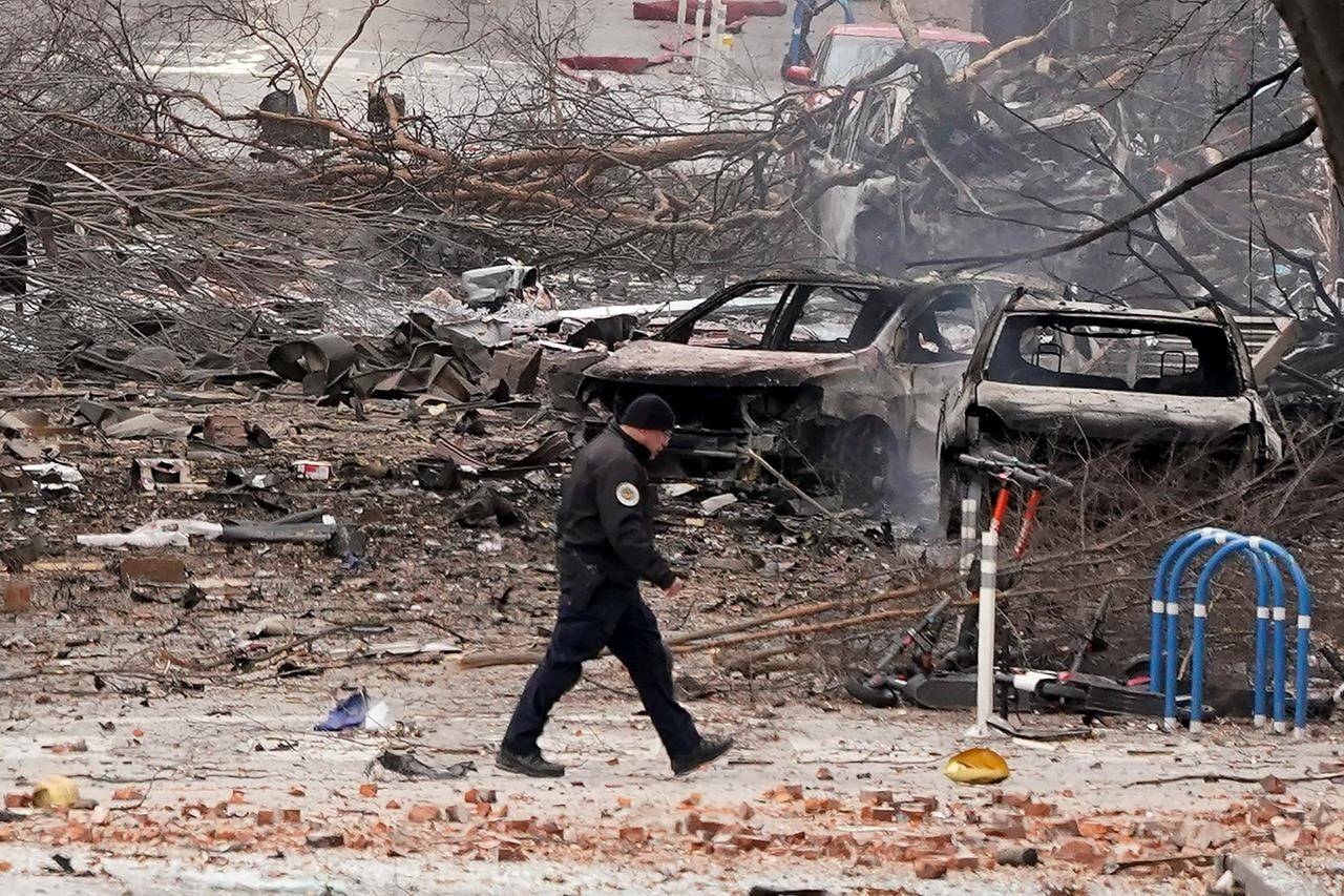 A law enforcement member walks past damage from an explosion in downtown Nashville, Tenn., Friday, Dec. 25, 2020. Buildings shook in the immediate area and beyond after a loud boom was heard early Christmas morning. (AP Photo/Mark Humphrey)