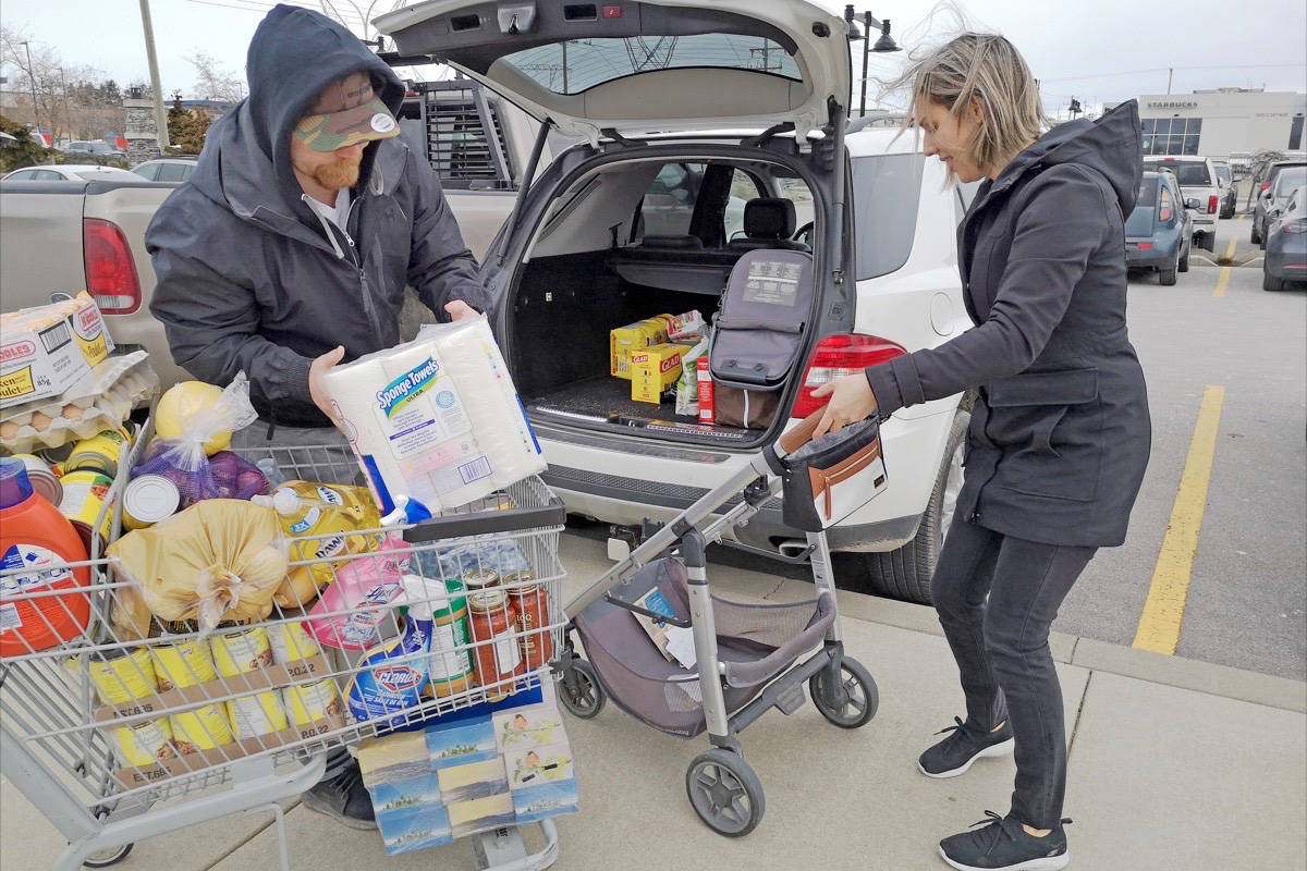 Rob and Sarah Thibault load their vehicle after stocking up on bottled water, canned goods and bread-making supplies at the South Surrey Superstore, where some were waiting as long as an hour in line. (Tracy Holmes/Peace Arch News)