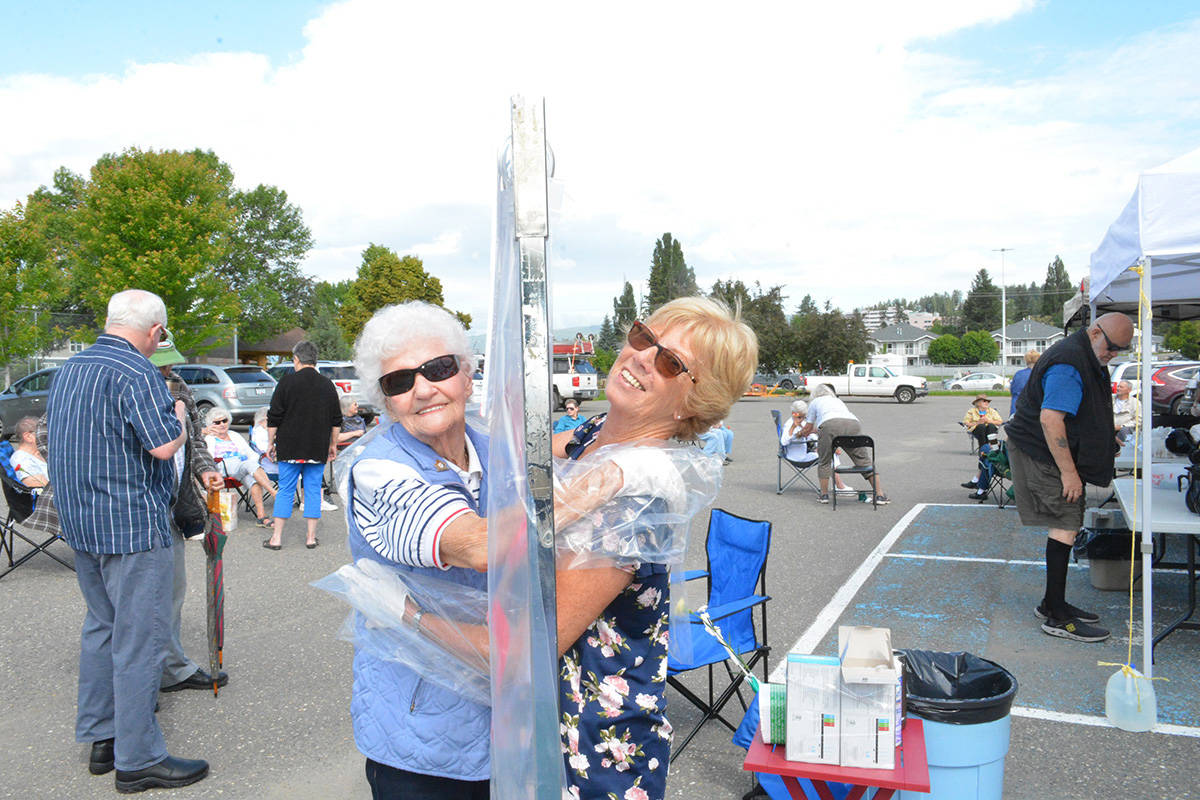 Tilly Knowles and Tina Derksen exchange a hug at the precautious station provided during a parking lot coffee house hosted by the Old Age Pensioners Organization and the Seniors Activity Centre on Monday. (Monica Lamb-Yorski photo/Williams Lake Tribune)