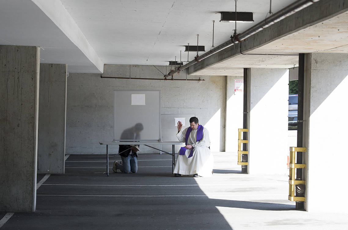 Priest in residence, Father Nick Meisl listens to a physically distanced confession in a parking garage at St. Patrick's Parish in Vancouver, Wednesday, April 8, 2020.  THE CANADIAN PRESS/Jonathan Hayward