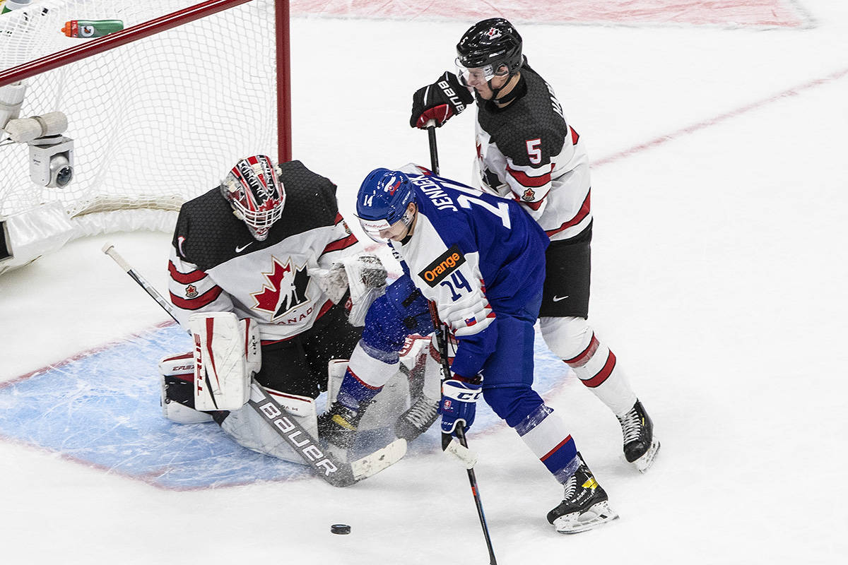 Canada's goalie Devon Levi (1) makes the save on Slovakia forward Dominik Jendek (14) as Thomas Harley (5) defends during second period IIHF World Junior Hockey Championship action in Edmonton on Sunday, Dec. 27, 2020. THE CANADIAN PRESS/Jason Franson