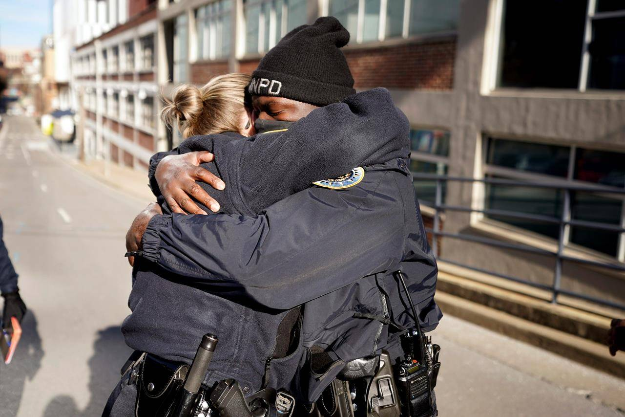 Nashville Police officers Brenna Hosey, left, and James Wells embrace after speaking at a news conference Sunday, Dec. 27, 2020, in Nashville, Tenn. The two officers are part of a group of officers credited with evacuating people before an explosion took place in downtown Nashville early Christmas morning. (AP Photo/Mark Humphrey)
