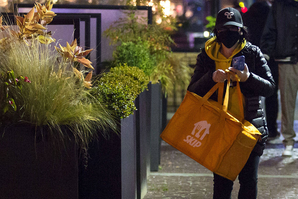 A food delivery person wears a face mask as they walk away from a downtown Vancouver restaurant with a pick-up on Thursday, Dec. 3, 2020. THE CANADIAN PRESS/Marissa Tiel