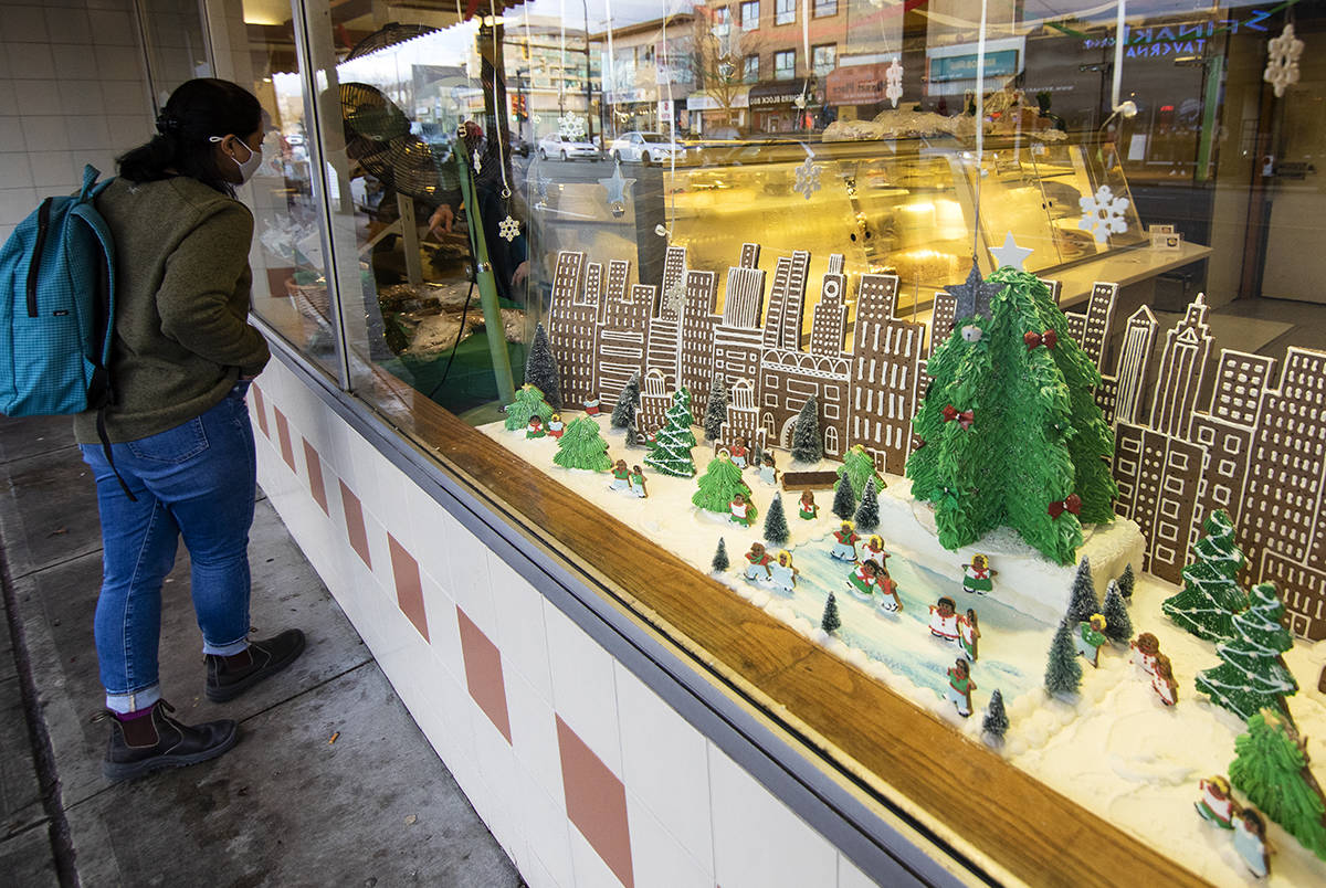A woman peers into a bakery's window, where a gingerbread city is displayed, in Burnaby, B.C. on Thursday, Dec. 17, 2020. THE CANADIAN PRESS/Marissa Tiel