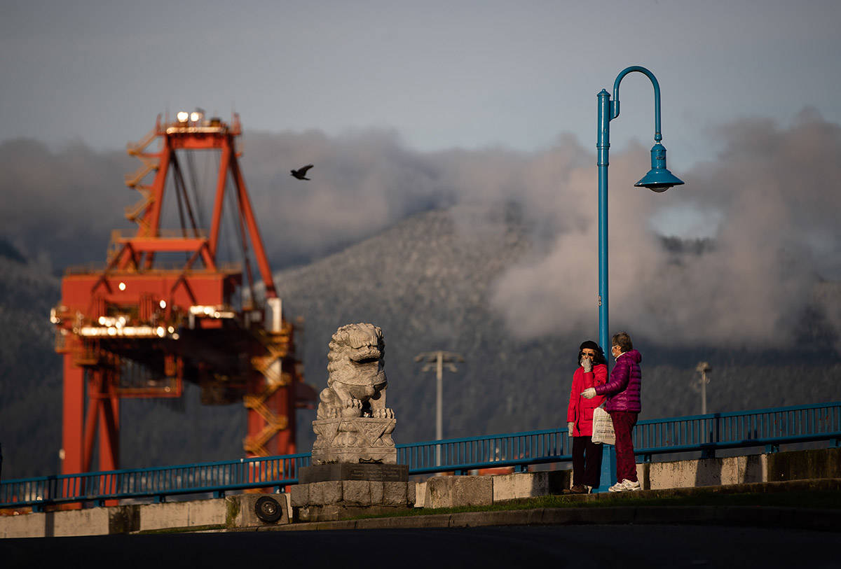 A woman wearing a face mask to curb the spread of COVID-19 speaks with a woman using a plastic bag to cover her mouth, as the snow-covered north shore mountains and a gantry crane at the Port of Vancouver are seen in the distance, in Vancouver, on Tuesday, December 22, 2020. THE CANADIAN PRESS/Darryl Dyck