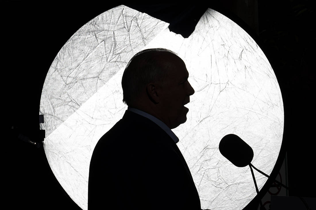 NDP Leader John Horgan is silhouetted against a reflector as he addresses the media during an election campaign stop in Coquitlam, B.C. Tuesday, September 29, 2020. THE CANADIAN PRESS/Jonathan Hayward