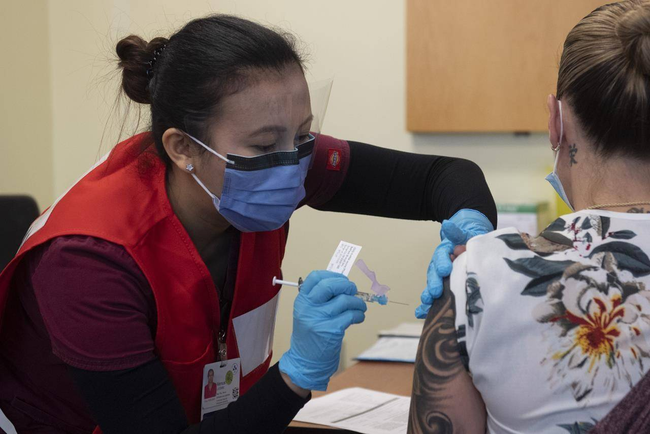 Nurse Venus Lucero administers the first Pfizer-BioNTech COVID-19 vaccine at the Ottawa Hospital to Jo-Anne Miner at a vaccination clinic, Tuesday December 15, 2020 in Ottawa. THE CANADIAN PRESS/Adrian Wyld