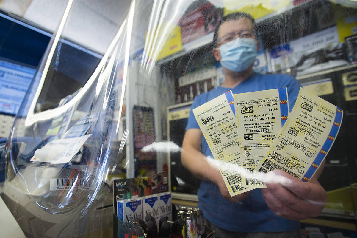 A convince store owner hands OLG 649 and Lotto Max tickets at his store during the COVID-19 pandemic in Mississauga, Ont., on Monday, May 25, 2020. Premier Doug Ford's government gives $500M loan to Ontario Lottery and Gaming. THE CANADIAN PRESS/Nathan Denette