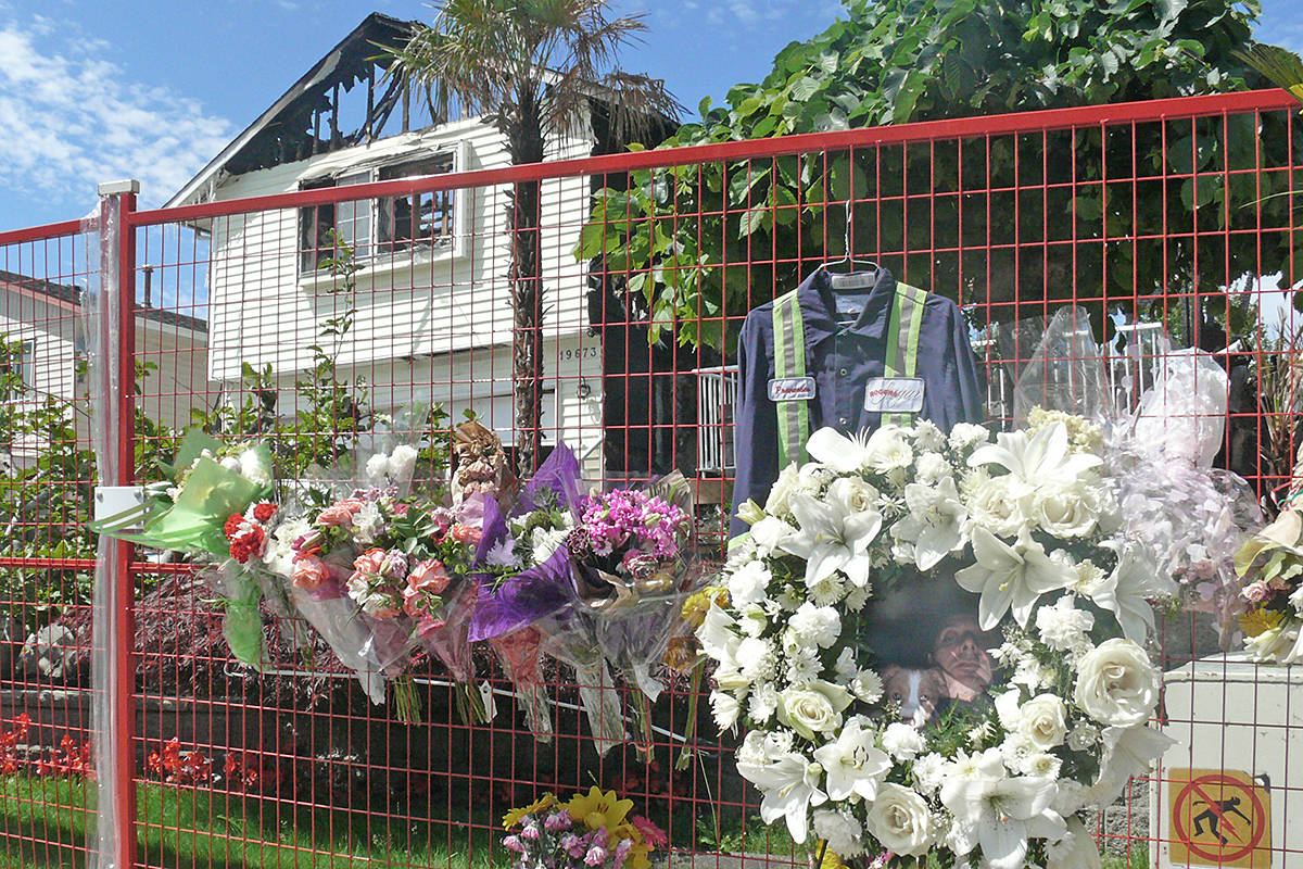 A flower-bedecked memorial to one three people who died at the scene of a suspicious house fire in Langley stands outside the burnt-out house in the 19600 block of Wakefield Drive on Monday, June 29, 2020. (Langley Advance Times files)