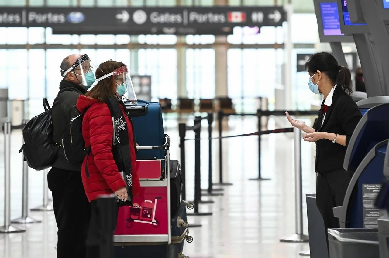 People wearing protective equipment check in at the international departures at Pearson International Airport during the COVID-19 pandemic in Toronto on Monday, December 14, 2020. THE CANADIAN PRESS/Nathan Denette
