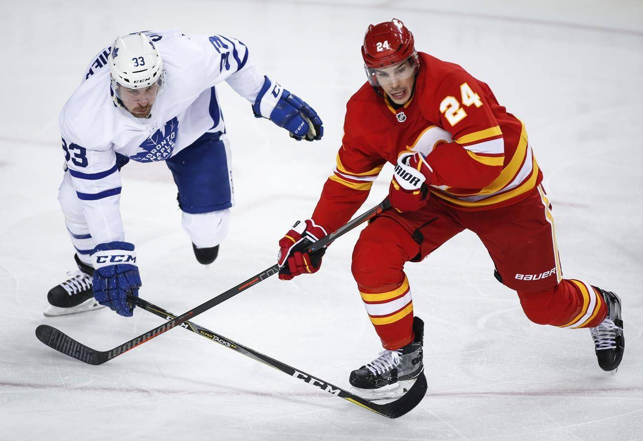 Toronto Maple Leafs' Frederik Gauthier, left, and Calgary Flames' Travis Hamonic chase the puck during third period NHL hockey action in Calgary on March 4, 2019. Hamonic has signed a profeesional tryout contract with the Vancouver Canucks. THE CANADIAN PRESS/Jeff McIntosh
