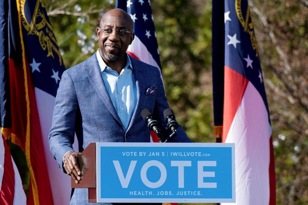 FILE - In this Dec. 21, 2020, file photo Democratic U.S. Senate challenger the Rev. Raphael Warnock speaks during a rally in Columbus, Ga. with Vice President-elect Kamala Harris and fellow Democratic U.S. Senate challenger Jon Ossoff. (AP Photo/Ben Gray, File)