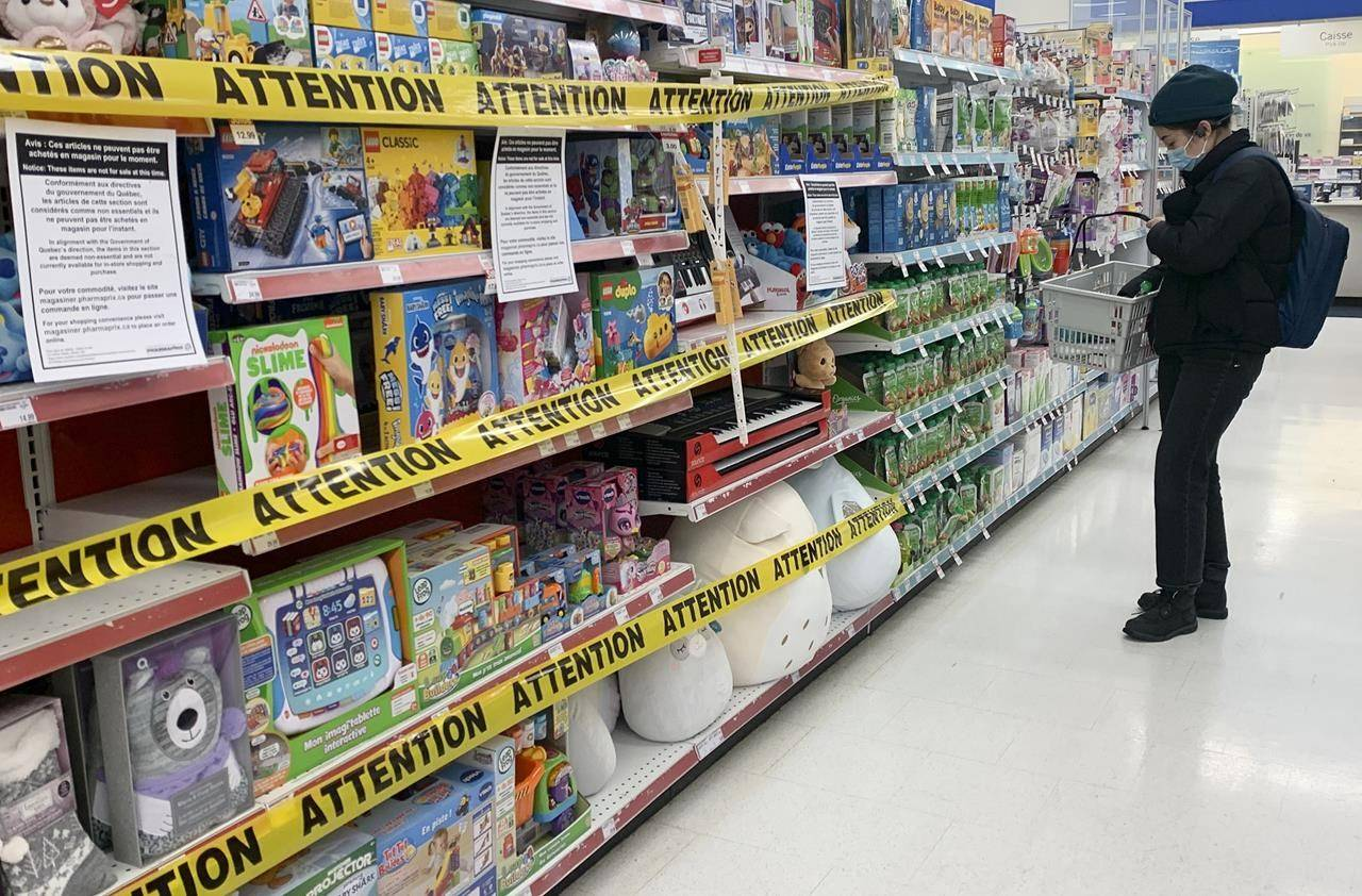 Tape is shown on shelves preventing the sale of certain products at a pharmacy in Montreal, Sunday, January 3, 2021, as the COVID-19 pandemic continues in Canada and around the world. THE CANADIAN PRESS/Graham Hughes