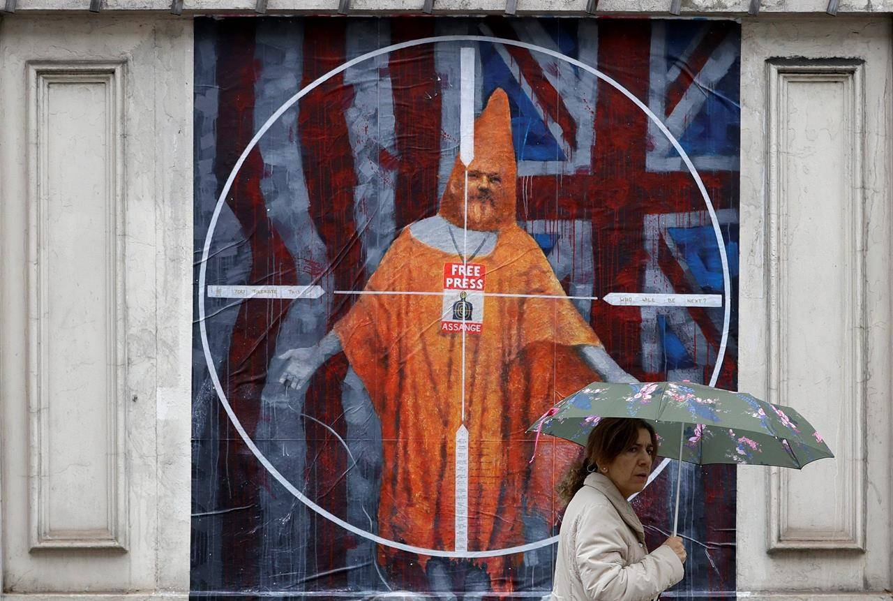 FILE - In this Monday Oct. 21, 2019 file photo a pedestrian passes street art depicting Julian Assange near Westminster Magistrates' Court in London where Assange is expected to appear as he fights extradition to the United States on charges of conspiring to hack into a Pentagon computer, in London. (AP Photo/Kirsty Wigglesworth, File)