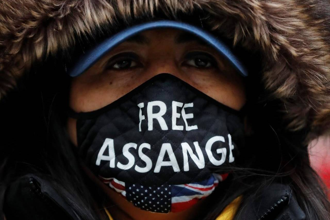 """A Julian Assange supporter wears a face mask bearing his name outside the Old Bailey in London, Monday, Jan. 4, 2021. Judgement is to be made by Judge Vanessa Baraitser on Julian Assange's his extradition hearing to the US. Assange has been charged under the US's 1917 Espionage Act for """"unlawfully obtaining and disclosing classified documents related to the national defence"""".(AP Photo/Frank Augstein)"""