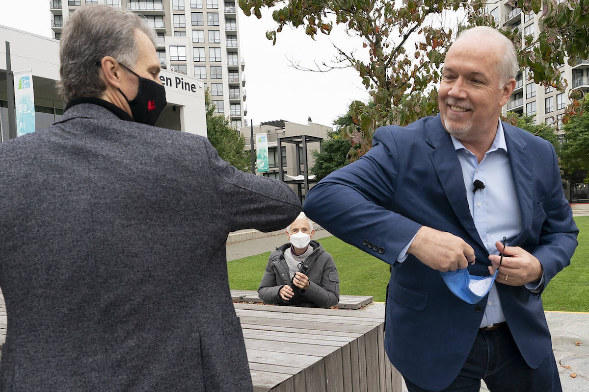 NDP leader John Horgan greets Coquitlam-Burke Mountain candidate Fin Donnelly in Coquitlam, B.C., Tuesday in the final days of his snap election campaign, October 20, 2020. THE CANADIAN PRESS