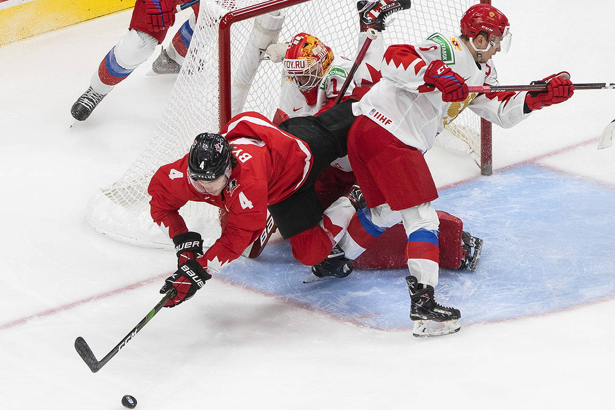 Canada's Bowen Byram (4) is knocked into Russia goalie Yaroslav Askarov (1) by defenseman Semyon Chistyakov (6) during first second period IIHF World Junior Hockey Championship action in Edmonton on Monday, Jan. 4, 2021. THE CANADIAN PRESS/Jason Franson