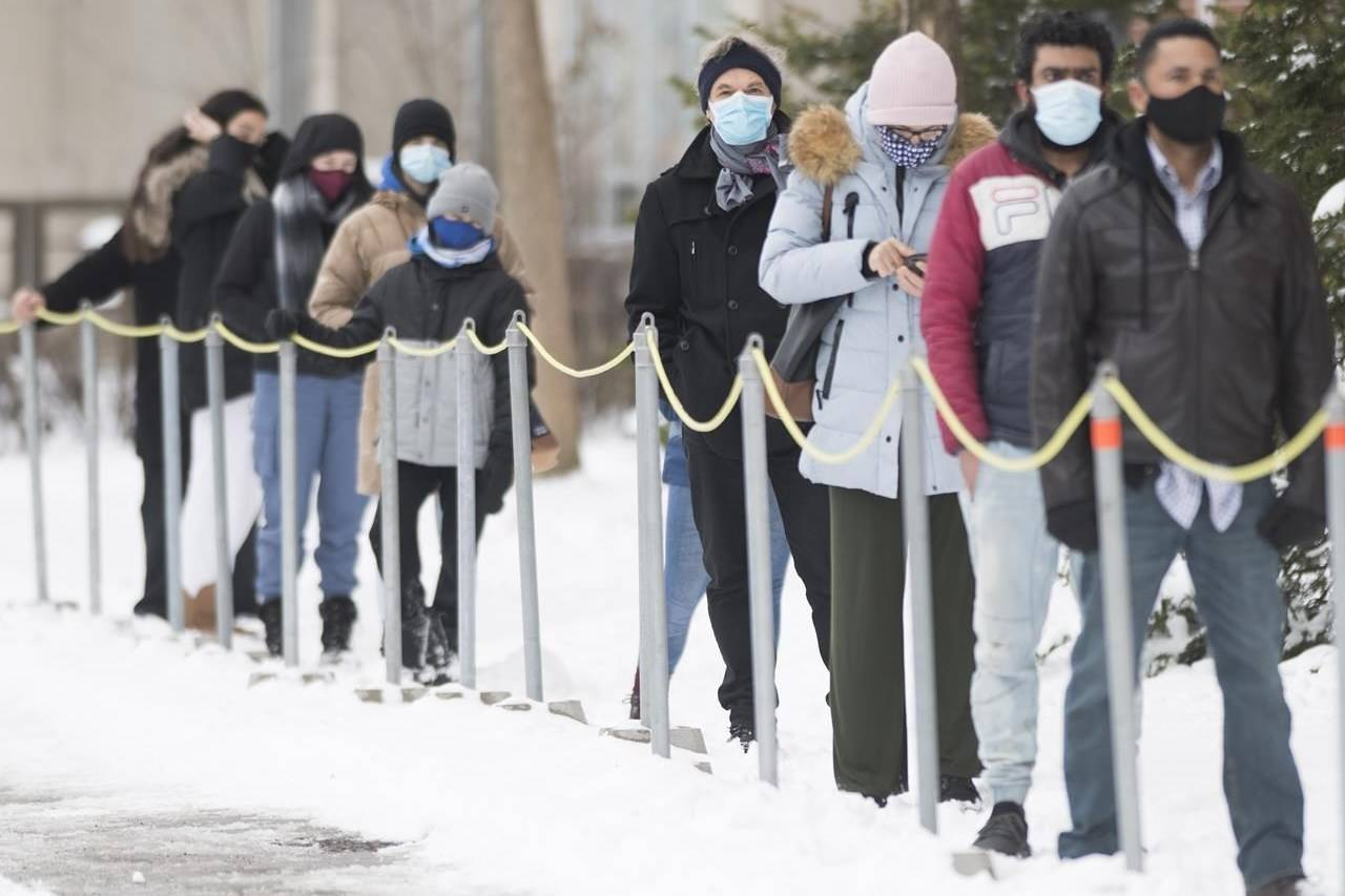 People wear face masks as they wait to be tested for COVID-19 at a clinic in Montreal, Sunday, Jan. 3, 2021. Canadian public health experts are raising alarm over an ongoing surge in COVID-19 cases and hospitalizations in several provinces. THE CANADIAN PRESS/Graham Hughes