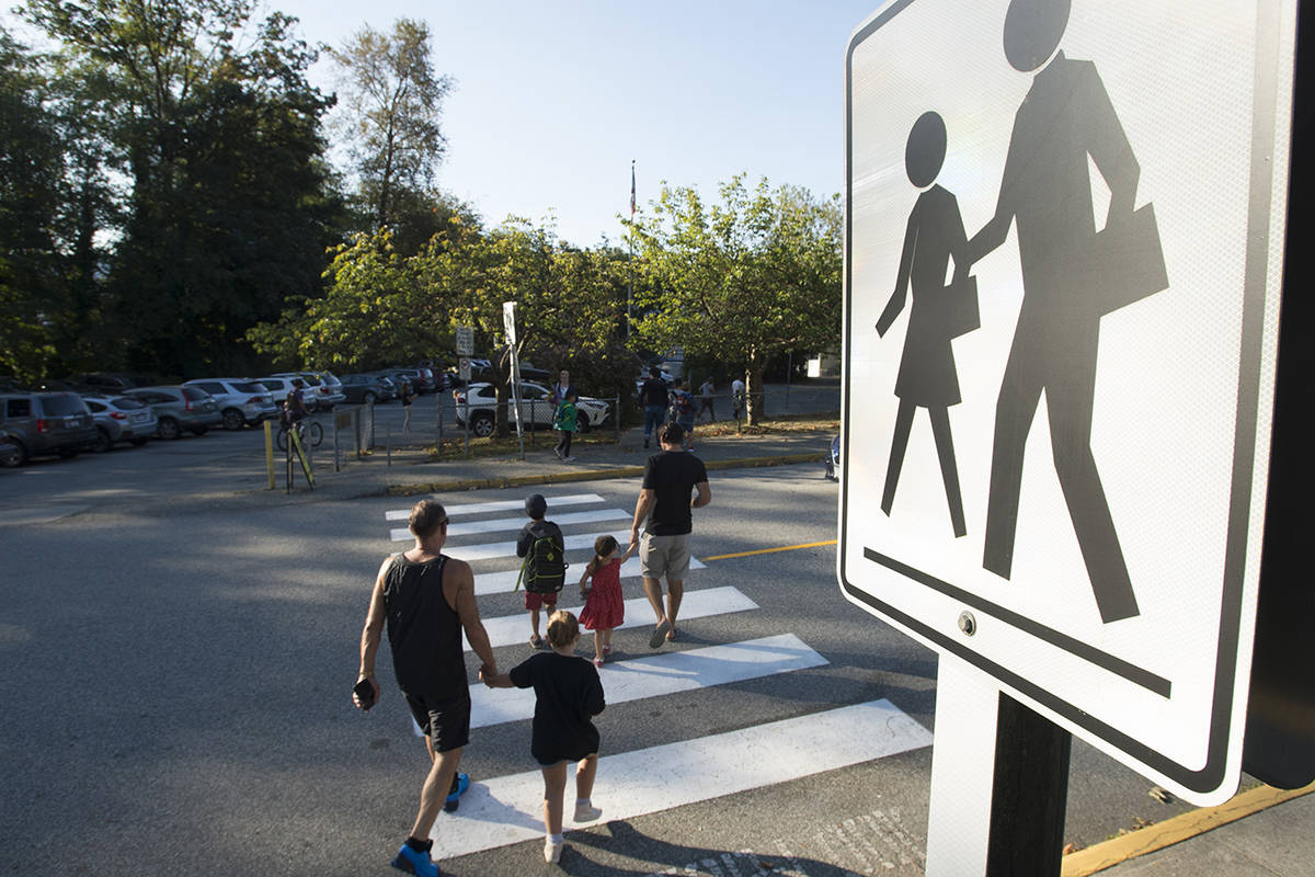 FILE – Children walk with their parents to Sherwood Park Elementary in North Vancouver for the first day back-to-school Thursday, September 10, 2020. THE CANADIAN PRESS/Jonathan Hayward