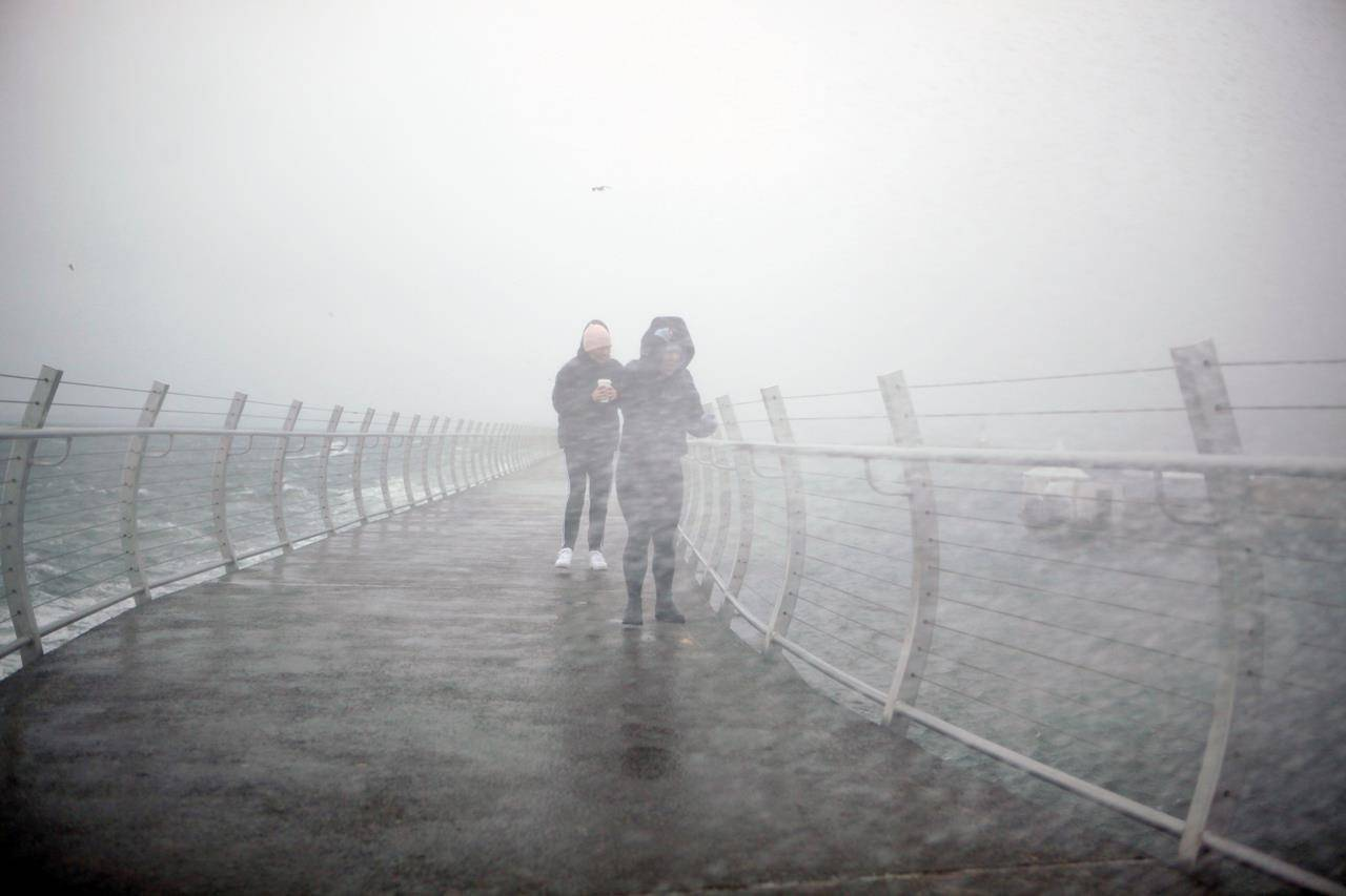 People brave strong winds along the Ogden Point breakwater during wind warnings issued by Environment Canada along the south coast as a frontal system pushes across Vancouver Island during the first major storm of the year in Victoria, Tuesday, Jan. 5, 2021. THE CANADIAN PRESS/Chad Hipolito