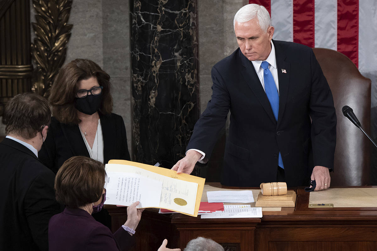 Vice President Mike Pence hands the electoral certificate from the state of Arizona to Sen. Amy Klobuchar, D-Minn., as he presides over a joint session of Congress as it convenes to count the Electoral College votes cast in November's election, at the Capitol in Washington, Wednesday, Jan. 6, 2021. (Saul Loeb/Pool via AP)
