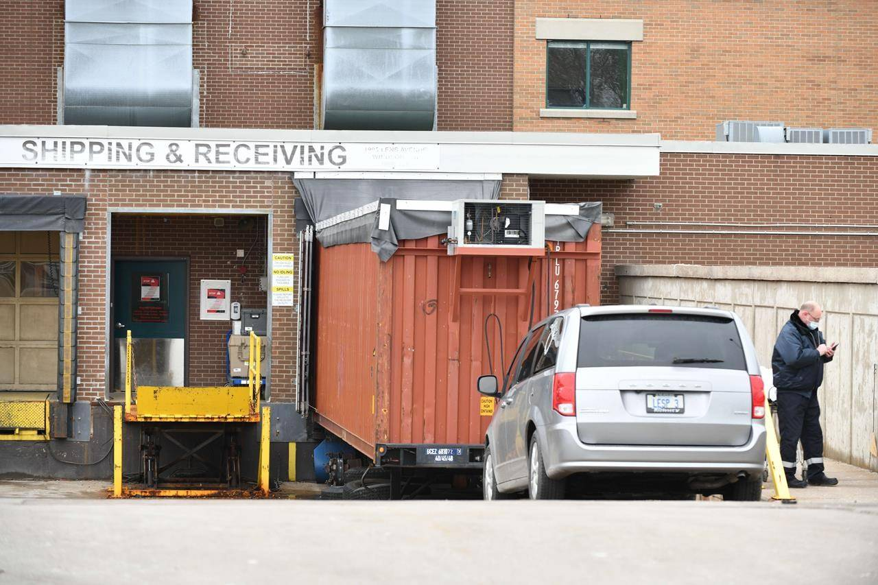 A grey minivan belonging to a local funeral home parks in front of a storage container that's been converted into a temporary morgue at the rear of Windsor Regional Hospital Met Campus in Windsor, Ont., Wednesday, January 6, 2021. THE CANADIAN PRESS/Rob Gurdebeke
