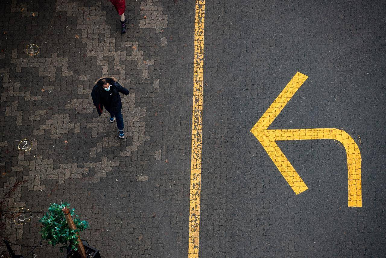 A person wearing a face mask to curb the spread of COVID-19 walks past a directional arrow painted on the road, in Vancouver, on Sunday, December 27, 2020. THE CANADIAN PRESS/Darryl Dyck