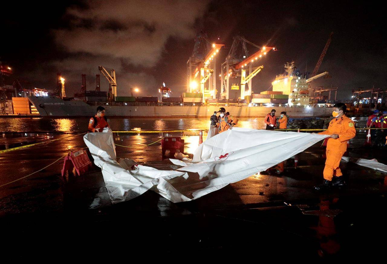 Members of National Search and Rescue Agency (BASARNAS) prepare an area where debris found in the waters where a Sriwijaya Air passenger jet has lost contact with air traffic controllers will be brought to be examined, at Tanjung Priok Port in Jakarta, Indonesia, early Sunday, Jan. 10, 2021. The Boeing 737-500 took off from Jakarta for Pontianak, the capital of West Kalimantan province on Indonesia's Borneo island with 56 passengers and six crew members onboard, and lost contact with the control tower a few moments later. (AP Photo/Dita Alangkara)