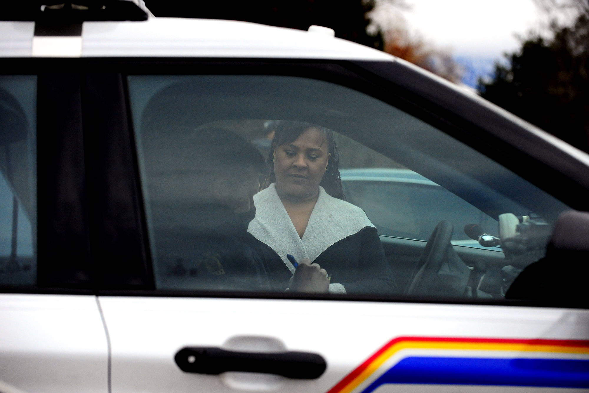 Heather Lucier, a pastor at Kelowna Harvest Fellowship, speaks to an RCMP officer outside of the church on Sunday, Jan. 10. (Michael Rodriguez - Capital News)