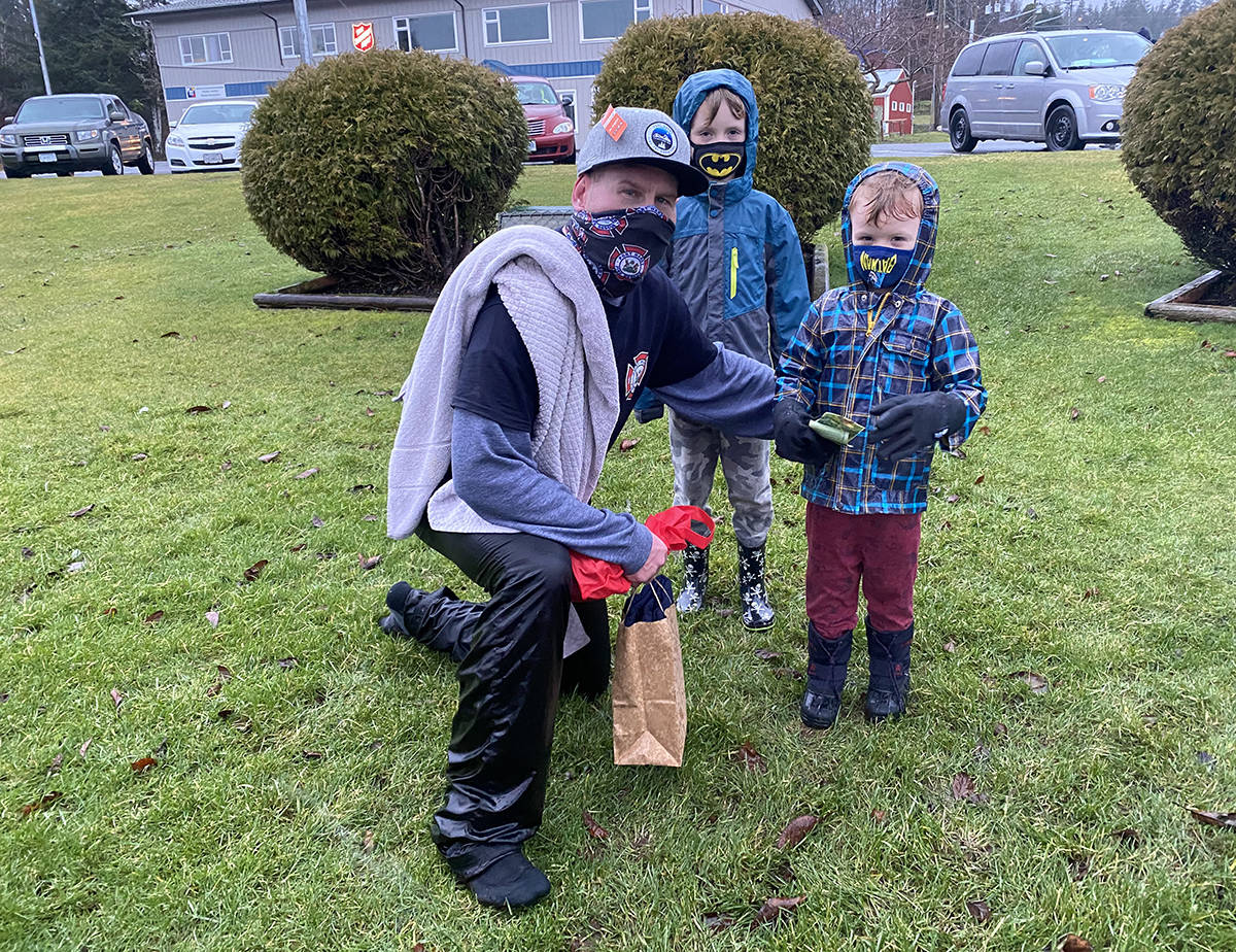 After jumping in the ocean, Dwayne Buckle was given donations from various people, including Weston Ireton (right) and his brother Beckett. Weston is now cancer free after a two-year battle with leukemia. (Tyson Whitney - North Island Gazette)