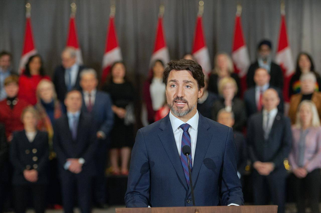 Prime Minister Justin Trudeau stands in front of his cabinet as he speaks to media during the final day of the Liberal cabinet retreat at the Fairmont Hotel in Winnipeg, Tuesday, Jan. 21, 2020. THE CANADIAN PRESS/Mike Sudoma