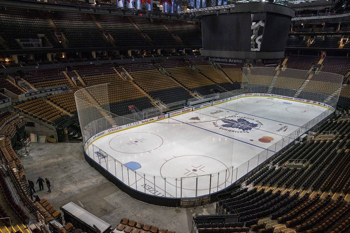 FILE – Workers stand by after pausing arena assembly for the Maple Leafs NHL hockey game against the Nashville Predators at Scotiabank Arena in Toronto on Thursday March 12, 2020. Since early March, the novel coronavirus has affected almost every decision facing the NHL. THE CANADIAN PRESS/Frank Gunn