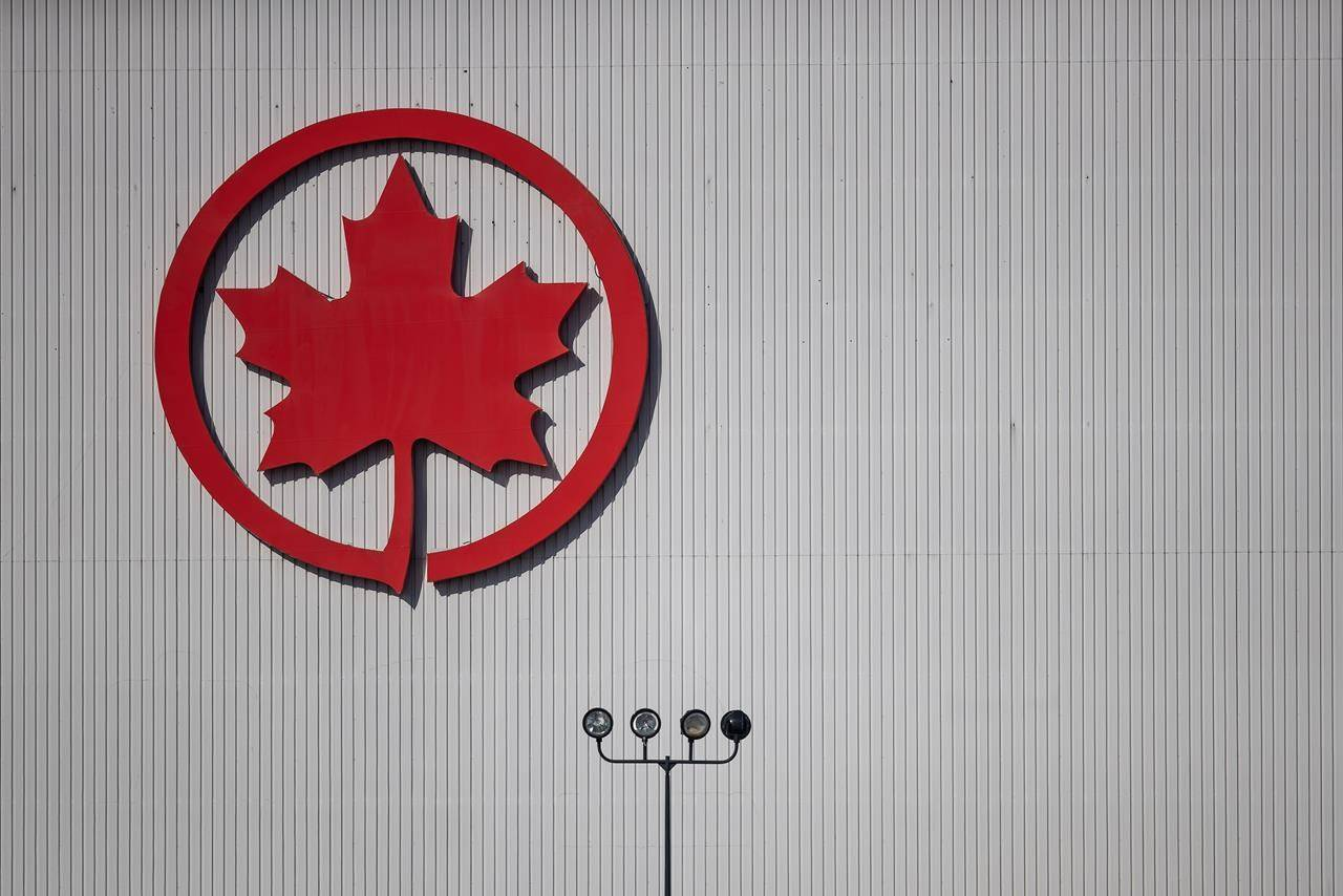 The Air Canada logo is seen on a hangar at Vancouver International Airport, in Richmond, B.C., on Friday, March 20, 2020. Air Canada has advised airports in Atlantic Canada that it will suspend more routes in the region until further notice. THE CANADIAN PRESS/Darryl Dyck