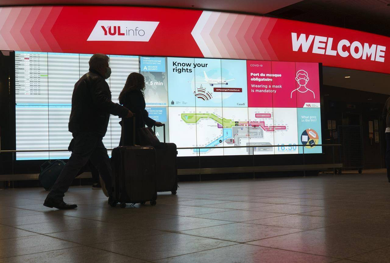 A couple makes their way through Montreal Trudeau Airport in Montreal, on Thursday, January 7, 2021. Canada's new testing requirement for international travellers has prompted hundreds of people to miss flights in the first week of the program's rollout.THE CANADIAN PRESS/Paul Chiasson