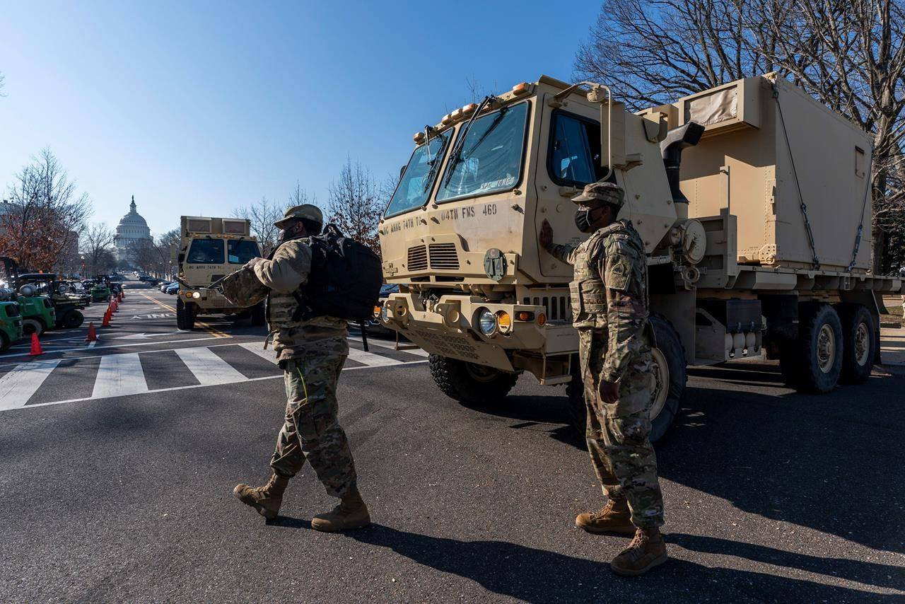 Members of the National Guard secure the perimeter around the Capitol, Wednesday, Jan. 13, 2021, in Washington as the House of Representatives continues with its fast-moving House vote to impeach President Donald Trump, a week after a mob of Trump supporters stormed the U.S. Capitol. (AP Photo/Manuel Balce Ceneta)