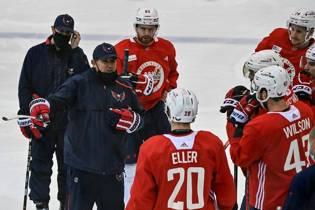 Washington Capitals head coach Peter Laviolette, center left, talks to his players during NHL hockey practice at the MedStar Capitals Iceplex in Arlington, Va., Monday, Jan. 4, 2021. (Ricky Carioti/The Washington Post via AP)