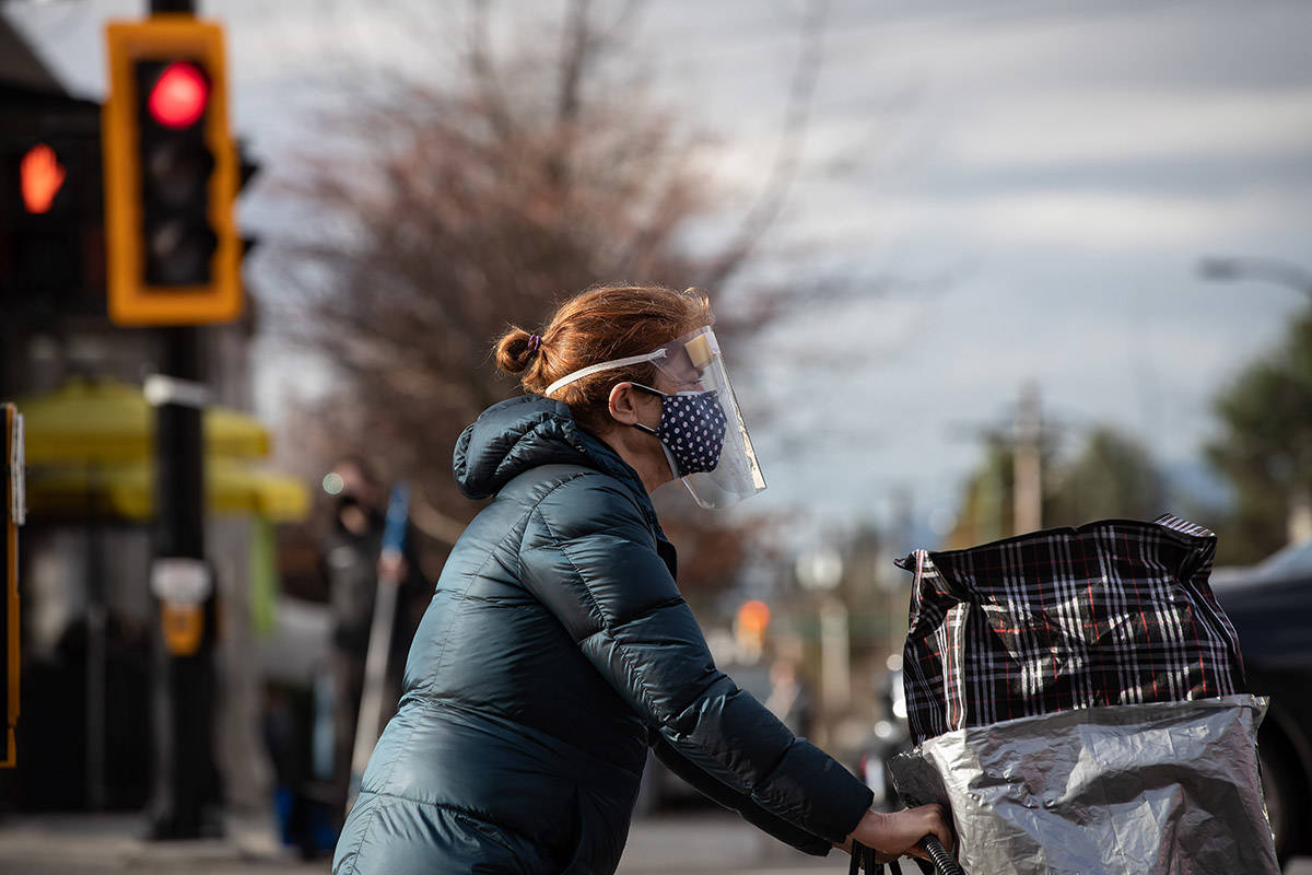 A woman wears a face mask and shield to curb the spread of COVID-19 while walking in North Vancouver, B.C., on Wednesday, January 6, 2020. THE CANADIAN PRESS/Darryl Dyck