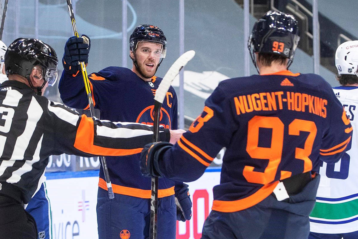 Edmonton Oilers' Connor McDavid (97) and Ryan Nugent-Hopkins (93) celebrate a goal against the Vancouver Canucks during second period NHL action in Edmonton, Thursday, Jan. 14, 2021. THE CANADIAN PRESS/Jason Franson