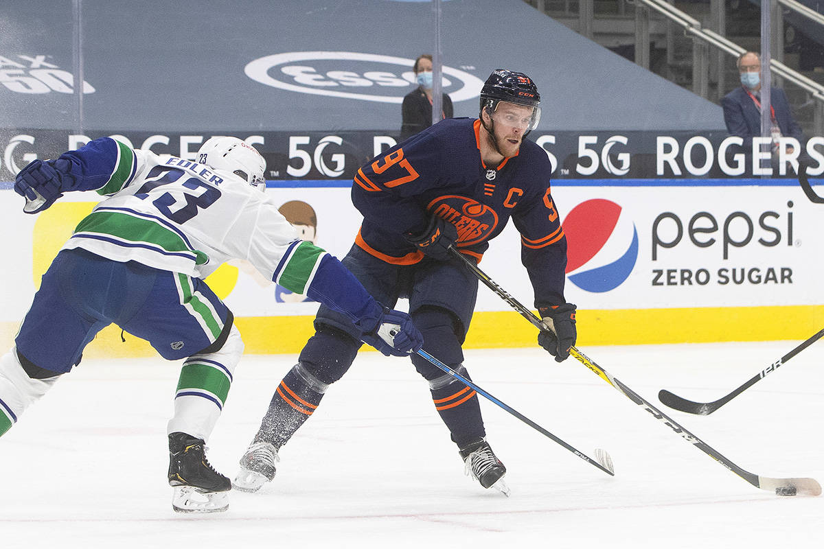Edmonton Oilers' Connor McDavid (97) makes a move to get past Vancouver Canucks' Alexander Edler (23) during second period NHL action in Edmonton on Thursday, Jan. 14, 2021. THE CANADIAN PRESS/Jason Franson
