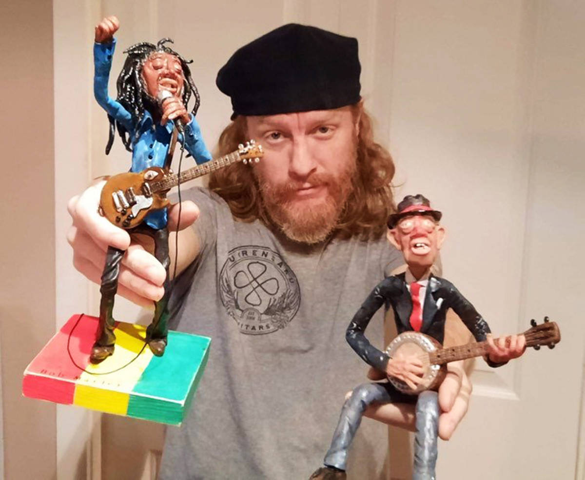"Brandon Isaak with two of the ""mini-legends"" he's made of clay. ""But I do not just do musicians or legends,"" says the Surrey-area musician. ""I did a series of hobos and the guy in my one hand is Homesick Joe. In the other hand a commissioned piece of Bob Marley."" (submitted photo: Cindy Mae)"