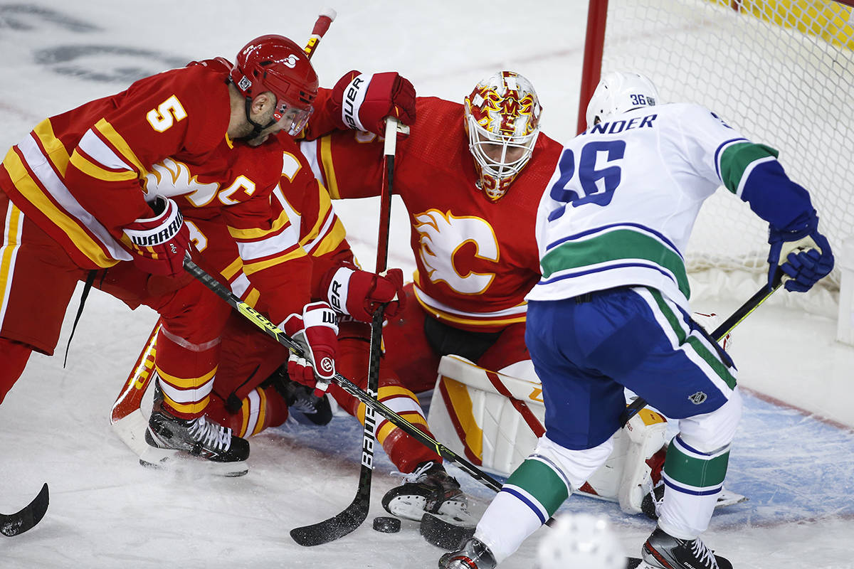 Vancouver Canucks' Nils Hoglander, right, scrambles for the puck in front of Calgary Flames goalie Jacob Markstrom, centre, and Mark Giordano during first period NHL hockey action in Calgary, Saturday, Jan. 16, 2021.THE CANADIAN PRESS/Jeff McIntosh