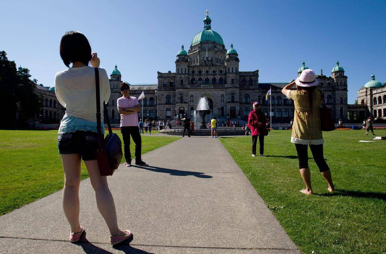Tourists take photographs outside the British Columbia Legislature in Victoria, B.C., on Friday August 26, 2011. A coalition of British Columbia tourism industry groups is urging the provincial government to not pursue plans to ban domestic travel to fight the spread of COVID-19. THE CANADIAN PRESS/Darryl Dyck