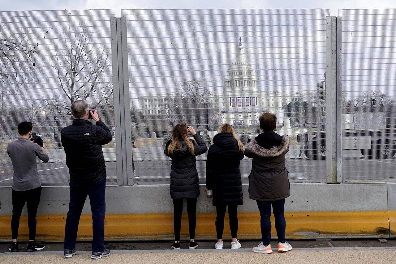 People take photos through the extensive security surrounding the U.S. Capitol in Washington, Friday, Jan. 15, 2021, ahead of the inauguration of president-elect Joe Biden and vice-president-elect Kamala Harris. THE CANADIAN PRESS/AP-Susan Walsh