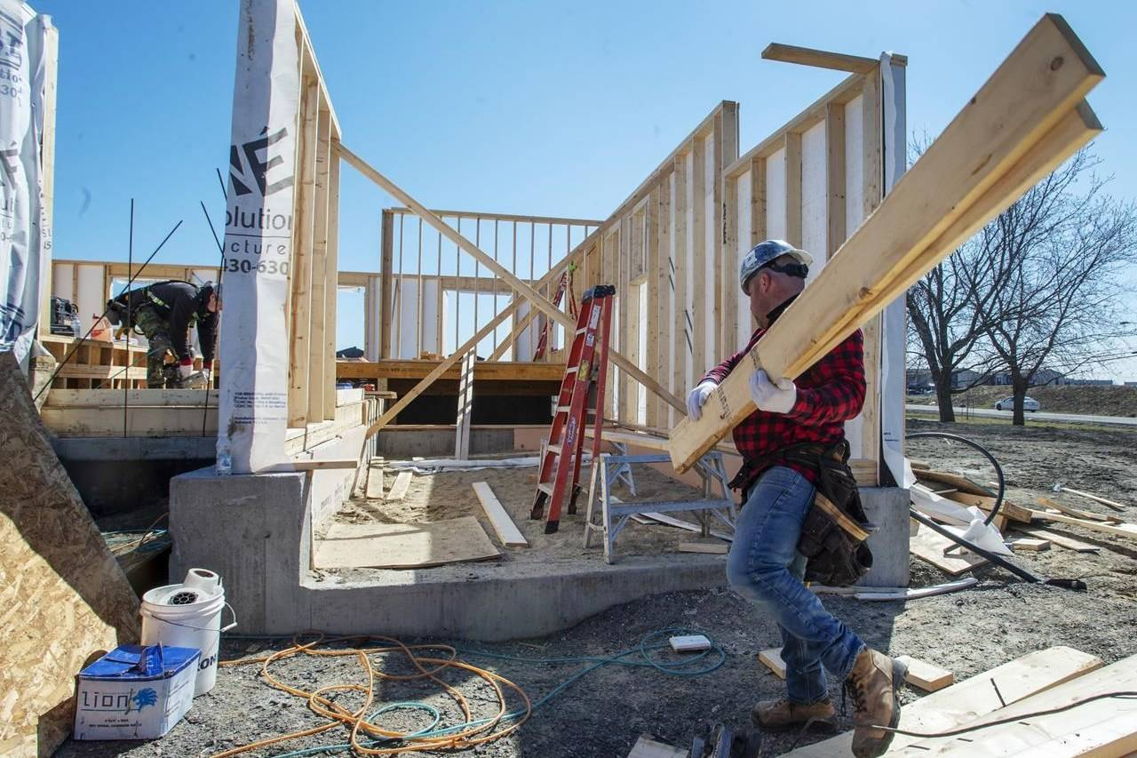Charles Rochfort, left, and Jonathan Grenier work on a home as Quebec lifts the ban on residential construction due to the COVID-19 pandemic Monday April 20, 2020 in Deux-Montagnes, Que. THE CANADIAN PRESS/Ryan Remiorz
