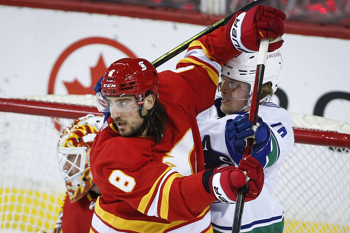 Vancouver Canucks' Elias Pettersson, right, battles for position with Calgary Flames' Chris Tanev during first period NHL hockey action in Calgary, Monday, Jan. 18, 2021.THE CANADIAN PRESS/Jeff McIntosh
