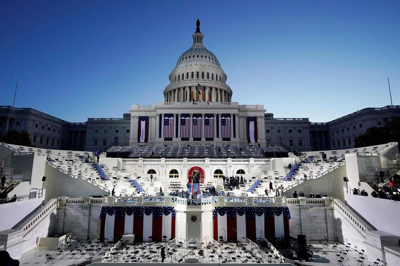 The U.S. Capitol and stage are lit as the Sun begins to rise before events get underway before the 59th Presidential Inauguration at the U.S. Capitol in Washington, Wednesday, Jan. 20, 2021. (AP Photo/Patrick Semansky, Pool)