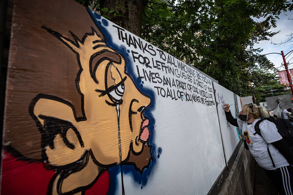 "A woman writes a message on a memorial mural wall by street artist James ""Smokey Devil"" Hardy during a memorial to remember victims of illicit drug overdose deaths on International Overdose Awareness Day, in the Downtown Eastside of Vancouver, on Monday, August 31, 2020. THE CANADIAN PRESS/Darryl Dyck"