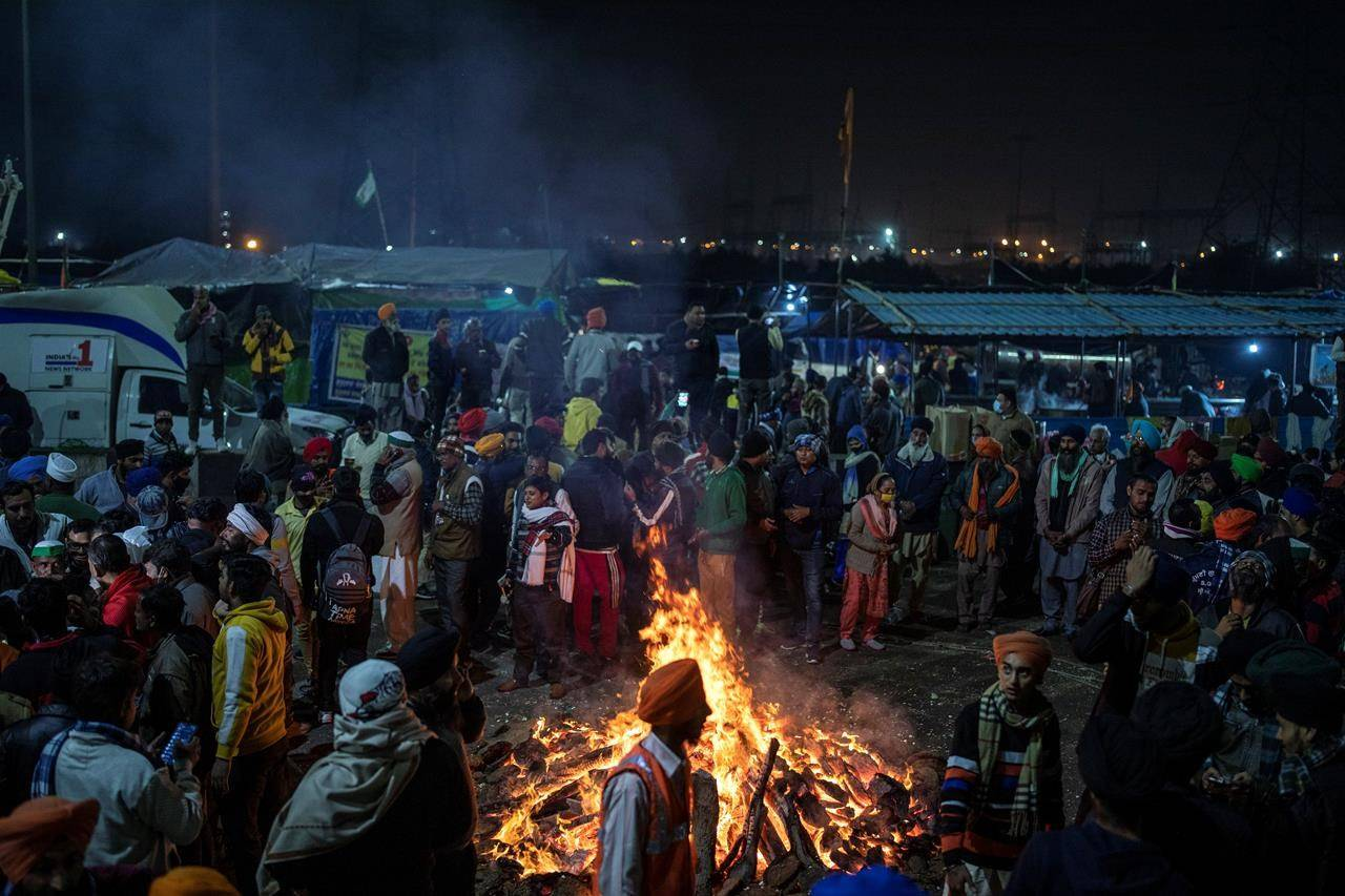 Protesting farmers and their families gather around a bonfire to mark the harvest festival, which is called Lohri, on a blocked highway in protest against new farm laws on the outskirts of New Delhi, India, Wednesday, Jan. 13, 2021. Changes in India's farm laws could potentially open up one of the world's most populous markets and are being closely watched by Canada's agricultural and economic sectors, say experts. THE CANADIAN PRESS/AP-Altaf Qadri