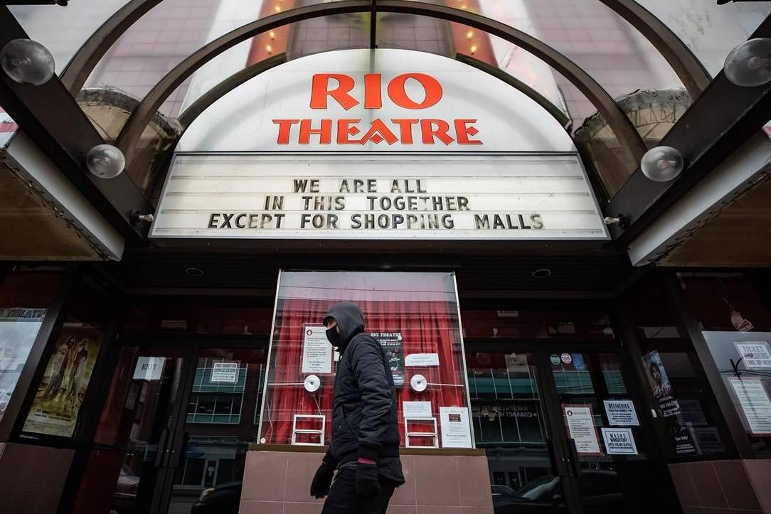 A person wearing a face mask to curb the spread of COVID-19 walks past the independent Rio Theatre, displaying a COVID-19 related message on its marquee in Vancouver on Sunday, December 6, 2020. THE CANADIAN PRESS/Darryl Dyck